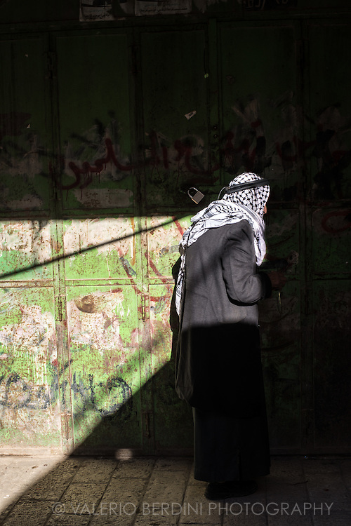 An Arab man with a Palestinian (black and white) keffiyeh walks pass the locked gate of a shop closed by Israeli Army in Hebron old city.