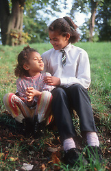 Two young girls sitting outside in park,