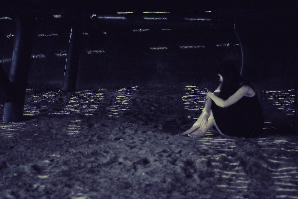 A young woman wearing a black dress sitting alone under a pier