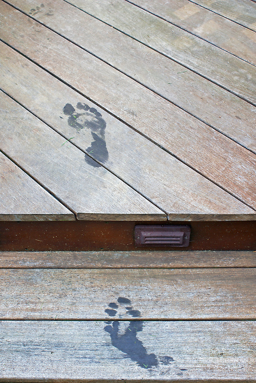 Wet foot prints on a wood deck reflect the impermanence of things.