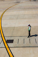 Female worker directs an All Nippon jet at Shanghai Pudong International Airport, Shanghai, China.