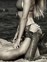 Artistic black and white portrait of a sexy young couple making love on sand at the beach