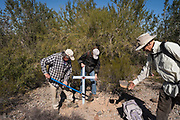 With assistance from Karen O'Hara and Ron Kovatch, artist Alvaro Enciso, left, secures a cross placed for a migrant named Celia Huaman Pilco whose remains were discovered on August 11, 2010 near a wash in the desert northwest of Tucson.
