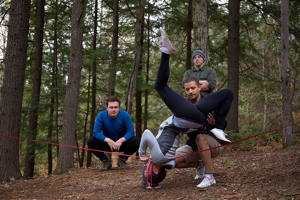 """While others participate in the afternoon worship service elsewhere, Bianca Inirio, of Cambridge, Mass., practices a slackline maneuver while supported by her husband, Hector Inirio, as Dan Walsh and Ethan Sanborn, both of Concord, N.H., watch at Church of the Woods in Canterbury, N.H., on April 30, 2017. """"They are doing Church of the Woods in their own way,"""" said Rev. Steve Blackmer of the activity. (Photo by Geoff Hansen)"""