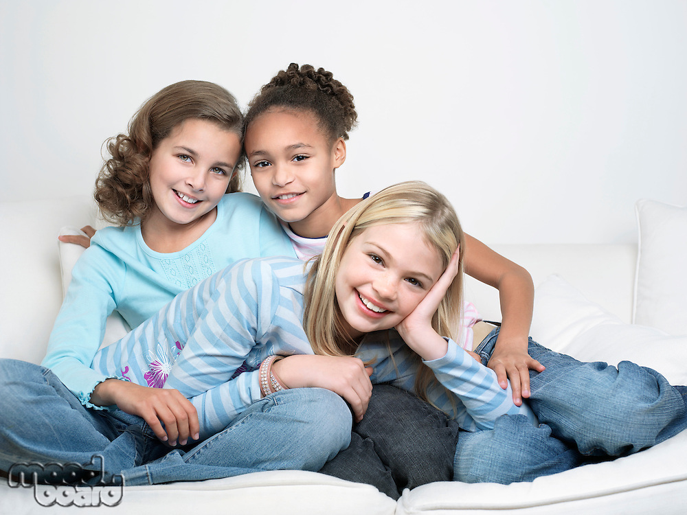 Young Friends sitting leaning on one another smiling