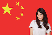 Portrait of smiling mixed race young woman against Chinese flag