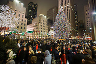 People gather to view the Rockefeller Center Christmas Tree