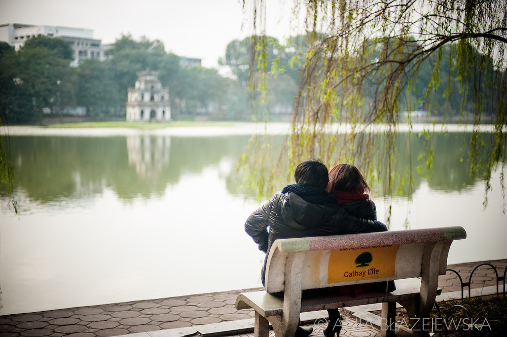 Vietnam, Hanoi. Couple sit on a bench at Hoan kiem Lake, one of the most scenic spots in the old Hanoi.