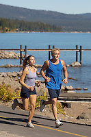 Couple jogging beside lake