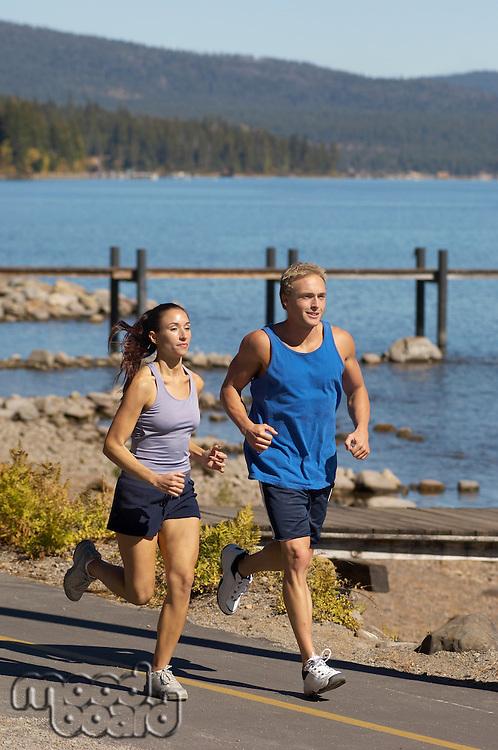 Couple jogging beside lake