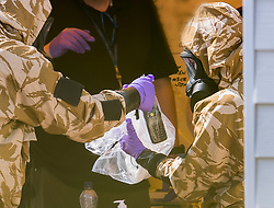 © Licensed to London News Pictures. 06/07/2018. Amesbury, UK. Police officers in protective suits and gas masks decontaminates a radio after gathering evidence inside a house in Muggleton Road, Amesbury where a couple, named locally as Dawn Sturgess, 44, and her partner Charlie Rowley, 45, were taken ill on Saturday 30th June 2018. Police have confirmed that the couple have been in contact with Novichok nerve agent. Former Russian spy Sergei Skripal and his daughter Yulia were poisoned with Novichok nerve agent in nearby Salisbury in March 2018. Photo credit: Peter Macdiarmid/LNP
