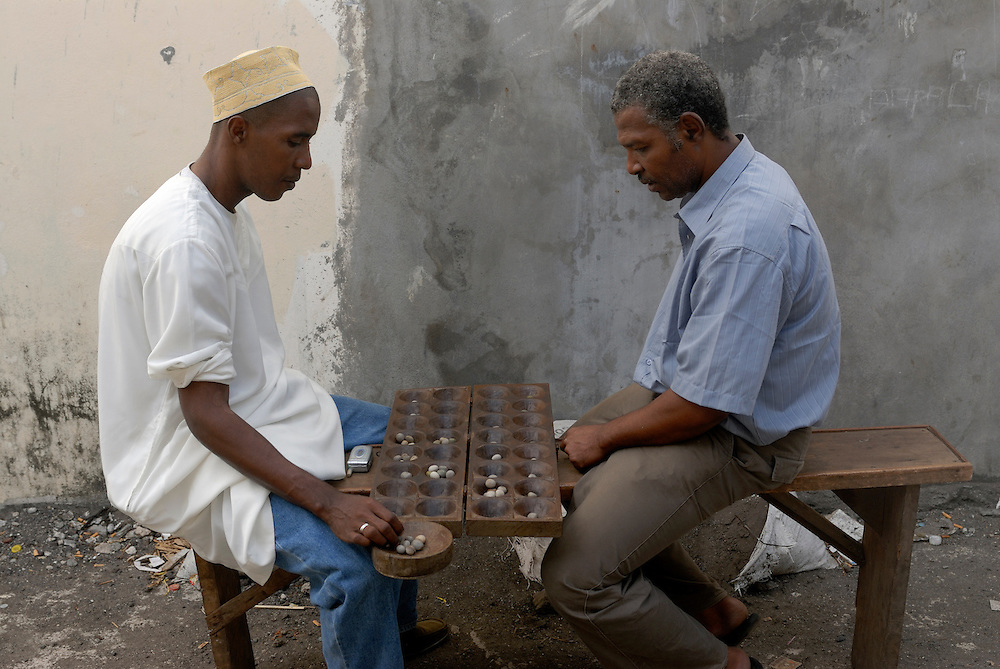 Two dark skinned men are playing a game. Comores. Grand Comore. Moroni.