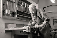 man in woodworking shop planing a board in a vise