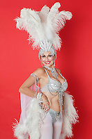 Portrait of senior woman in showgirl's outfit and feather headpiece over red background