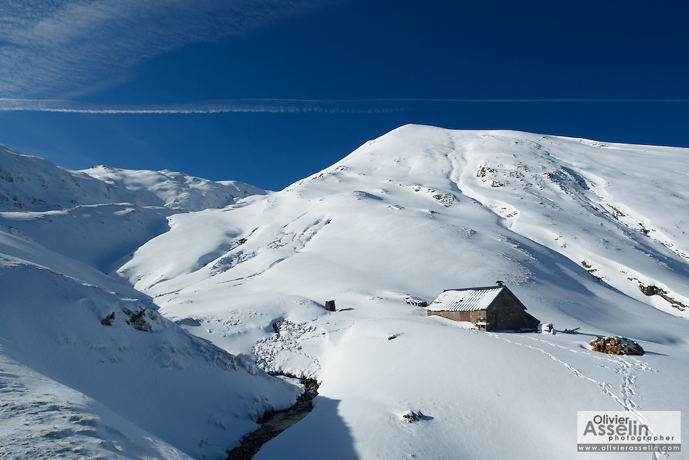 Mountain shelter in snowy mountain landscape near Col de Pause, Ariege, Pyrenees, France.