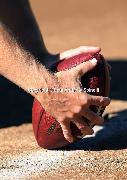 An Oakland Raiders player gets set to snap the football during the 2014 NFL preseason football game against the Detroit Lions on Friday, Aug. 15, 2014 in Oakland, Calif. The Raiders won the game 27-26. ©Paul Anthony Spinelli