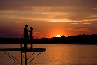 Couple sharing a tender moment on a dock with a beautiful sunset in the background.