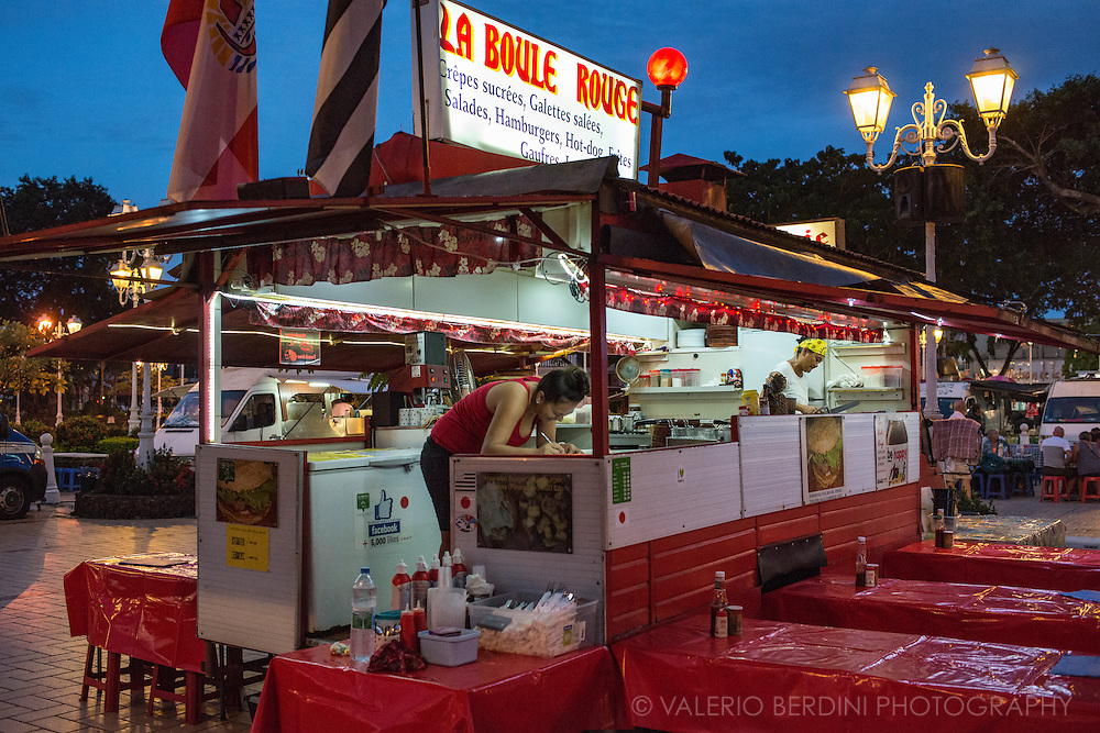 Roulottes are a traditional place to eat street food in French Polynesia. Campervans adapted to mobile restaurant opena t night in the centre of Papeete and biggest village in the country.