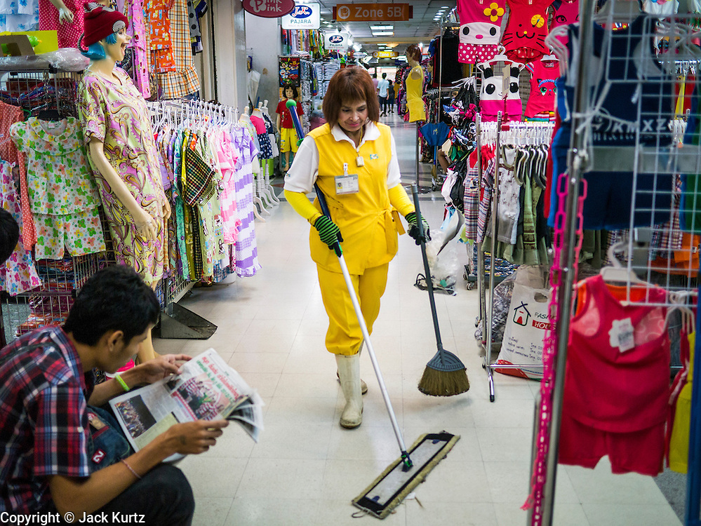 30 MAY 2013 - BANGKOK, THAILAND:   A cleaner works in the hallway of Bobae Tower in Bangkok. Bobae Market is a 30 year old famous for fashion wholesale and is now very popular with exporters from around the world. Bobae Tower is next to the market and  advertises itself as having 1,300 stalls under one roof and claims to be the largest garment wholesale center in Thailand.    PHOTO BY JACK KURTZ