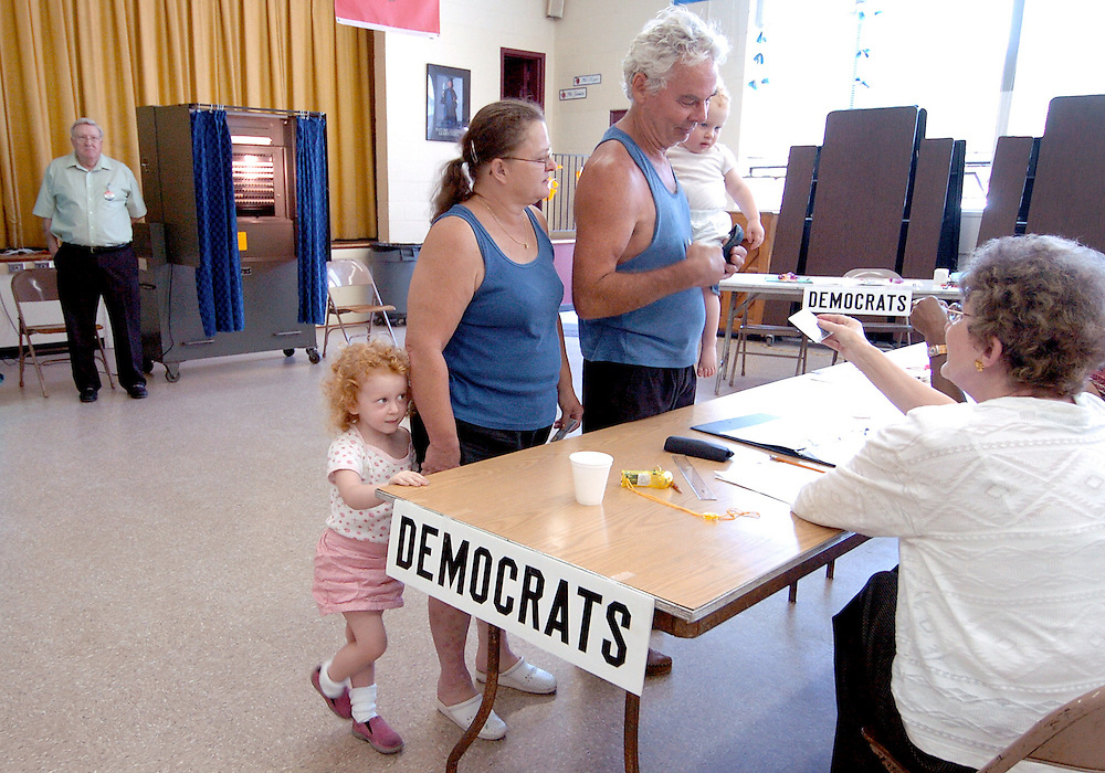 Charlotte and Barry Miron of East Hartford with granddaughters Jamie Lynn Thorpe, left, and Anna Thorpe, right, check in to vote in the statewide Democratic primary at Anna E. Norris School in East Hartford, Conn.  Voter traffic at this location has been very steady but not heavy according to volunteers.   A new poll showed the race tightening between Sen. Joe Lieberman and anti-war challenger Ned Lamont with Lamont holding a slight lead.  Lieberman has said he will run as an independent in the fall if defeated in the primary.