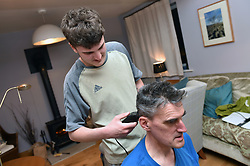 Life in coronavirus lockdown in the UK April 2020. Son cutting his father's hair using clippers.  Model released.