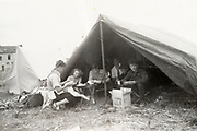 family in tent with a house in the background ca 1940s