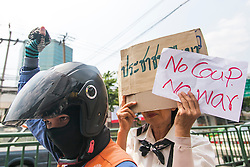 © Licensed to London News Pictures. 24/05/2014. Anti-Coup protestors hold up banners showing their displeasure towards the Military Junta following a Anti-Coup protest in Bangkok Thailand. The Royal Thai army announced a Military coup and have imposed a 10pm curfew.  Photo credit : Asanka Brendon Ratnayake/LNP