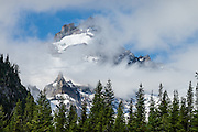 Little Tahoma Peak rises through fog in Mount Rainier National Park, Washington, USA. Little Tahoma is the third-highest peak in Washington (although it is a satellite peak of Mount Rainier). For vigorous training, hike a scenic 10 mile loop with 3200 feet ascent, from White River Campground up Glacier Basin Trail, to Second and First Burroughs, then back via Shadow Lake. Through mid July, be cautious of steep snow below Second Burroughs.