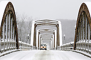 A vehicle travels on the RM Ruthven Bridge in Cotter, Arkansas, during snow storm.