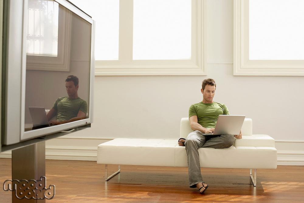 Man using laptop on modern sofa in modern apartment
