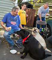 Lucky Jr with his fiance' Daisy Day by his side as they mingle with guests including John Senecal and accept a treat or two at Sanborn's Garage Saturday afternoon.  (Karen Bobotas/for the Laconia Daily Sun)