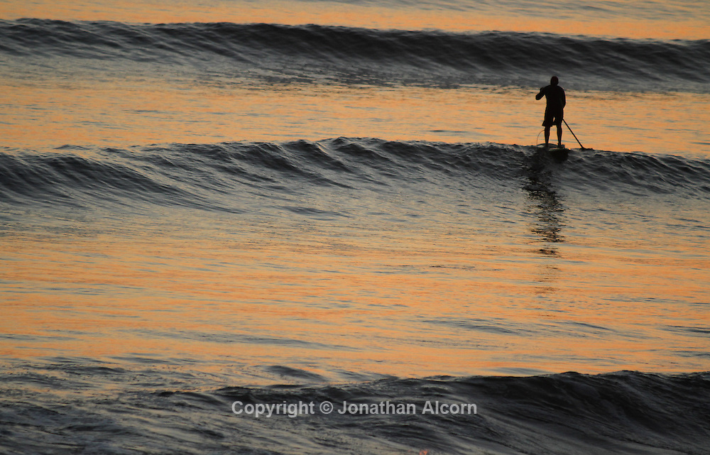 A paddle boarder paddles through the surf zone at sunset on a warm January winter day in Southern California.