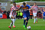 Bobby grant being challenged by Durrell Berry during the Sky Bet League 2 match between Cheltenham Town and Shrewsbury Town at Whaddon Road, Cheltenham, England on 25 April 2015. Photo by Alan Franklin.