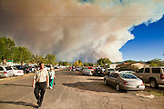 """03 JUNE 2011 - SPRINGERVILLE, AZ: The smoke column off the Wallow fire towers over people going to the community meeting about the fire in Eager Friday night. High winds and temperatures have continued to complicate firefighters' efforts to get the Wallow fire under control. The  mandatory evacuation order for Alpine was extended to Nutrioso, about 10 miles north of Alpine and early Friday morning fire was reported on the south side of Nutrioso. The fire grew to more than 106,000 acres early Friday with zero containment. A """"Type I"""" incident command team has been called in to manage the fire.   PHOTO BY JACK KURTZ"""