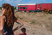 Child pointing at woman with tattoos and red dreadlocks near horses, BulgariaTek, Bulgaria August 2011