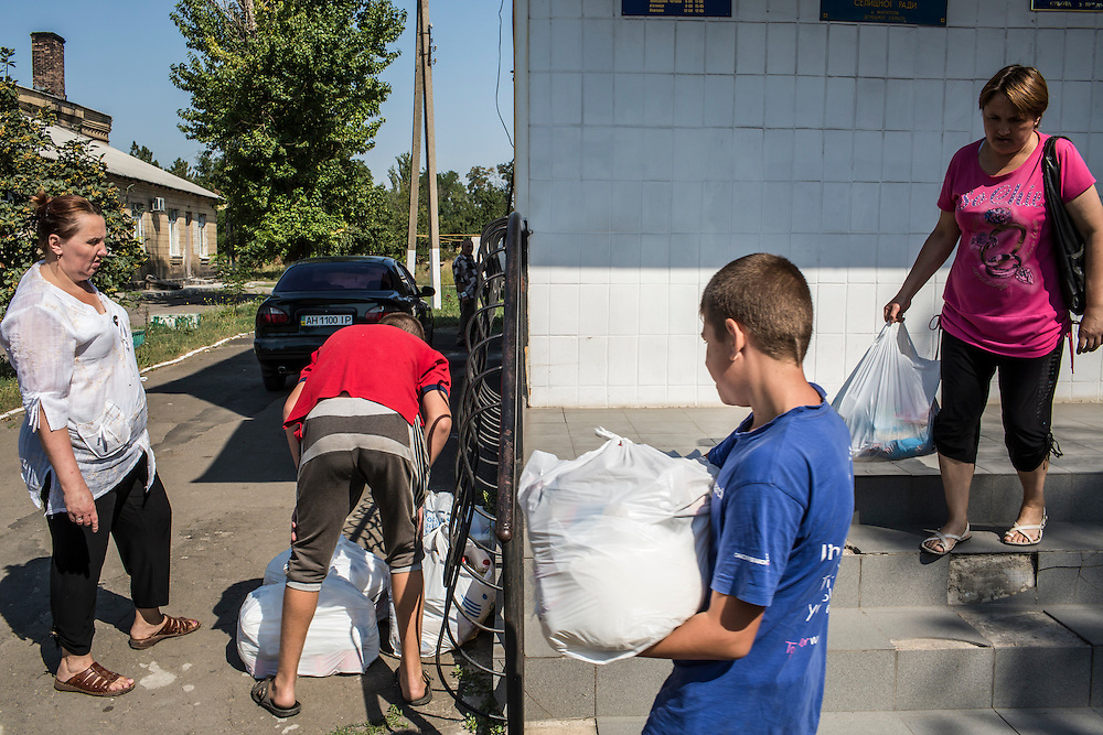SARTANA, UKRAINE - AUGUST 29, 2015: Residents receiving humanitarian aid carry bags of staple products at a distribution point in Sartana, Ukraine. The village of Sartana, on the northeastern outskirts of Mariupol, has been relatively close to the front line between Ukrainian and pro-Russian rebel forces, with many incidents of shelling damaging homes and injuring or killing civilians. CREDIT: Brendan Hoffman for The New York Times
