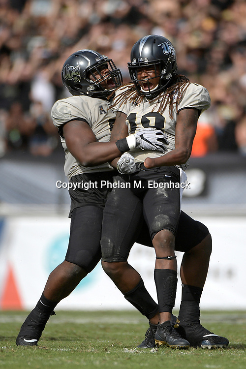 Central Florida linebacker Shaquem Griffin (18) celebrates after sacking Memphis quarterback Riley Ferguson as Central Florida defensive lineman Jamiyus Pittman (5) congratulates him during the first half of the American Athletic Conference championship NCAA college football game Saturday, Dec. 2, 2017, in Orlando, Fla. (Photo by Phelan M. Ebenhack)