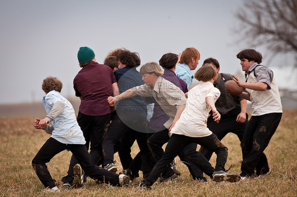 Amish play football in a farm field during the Annual Mud Sale to support the Fire Department  in Gordonville, PA.