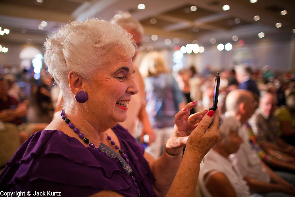 14 SEPTEMBER 2011 - SUN LAKES, AZ: Paula Gray (CQ) from Sun Lakes, uses her cell phone to take pictures during Mitt Romney's stop at the Oakwood Clubhouse at Sun Lakes Wednesday. Romney was one of the first of the 2012 Republicans running for the GOP Presidential nomination to come to Arizona. He campaigned Wednesday in Tucson and Sun Lakes and attended a private event in Tempe.     PHOTO BY JACK KURTZ