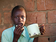 Children from Florence's family eating maize porridge before heading off to school. Before her training with Send a Cow the children were't having anything to eat in the mornings and some weren't even able to go to school because of a lack on school fees.