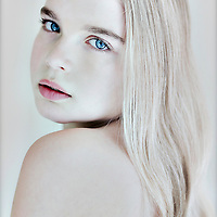 Close up of female youth with blonde hair and blue eyes looking over shoulder at camera