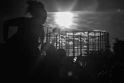 London, August 29th 2016. With the Kensal Green gasometer tower in the background, a woman makes a silhouette against the setting sun at the end of day two of Europe's biggest street party, the Notting Hill Carnival.