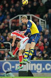 Stoke's Jonathan Walters challenges for the header with Arsenal's Per Mertesacker - Photo mandatory by-line: Dougie Allward/JMP - Mobile: 07966 386802 - 06/12/2014 - SPORT - Football - Stoke - Britannia Stadium - Stoke City v Arsenal - Barclays Premie League