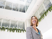 Business woman standing in atrium of office building low angle view