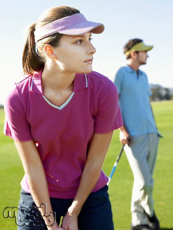 Two young golfers on course focus on woman