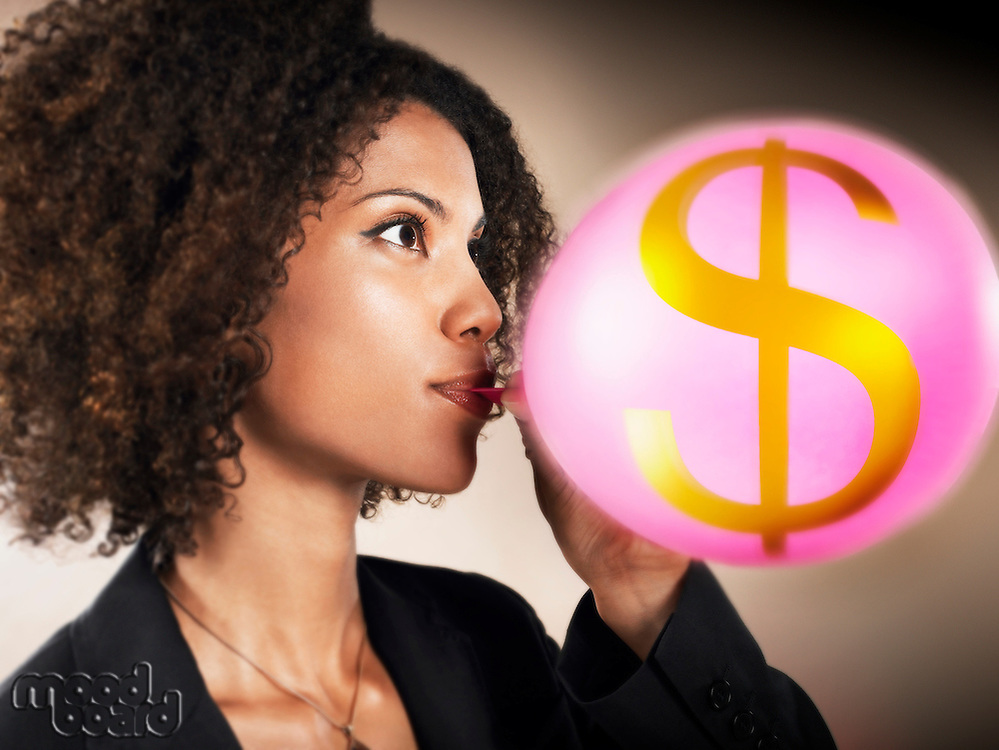 Businesswoman blowing up balloon with dollar sign on head and shoulders