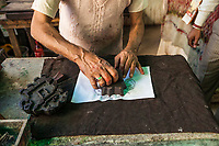 A craftman doing block printing on fabric in Jaipur, India.