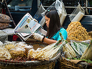 22 MARCH 2016 - BANGKOK, THAILAND:  A woman selling ginger reads the newspaper in her stall in the flower market. Many of the sidewalk vendors around Pak Khlong Talat, the Bangkok flower market, closed their stalls Monday. As a part of the military government sponsored initiative to clean up Bangkok, city officials announced new rules for the sidewalk vendors that shortened their hours and changed the regulations they worked under. Some vendors said the new rules were confusing and too limiting and most vendors chose to close Monday rather than risk fines and penalties. Many hope to reopen when the situation is clarified.        PHOTO BY JACK KURTZ