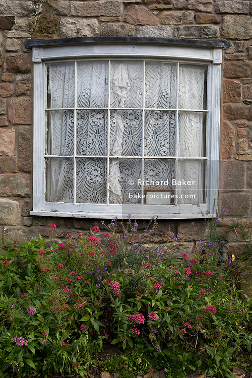 A rounded front window of a cottage on Holy Island, on 27th September 2017, on Lindisfarne Island, Northumberland, England. The small Lindisfarne population of just over 160 is swelled by the influx of over 650,000 visitors from all over the world every year. A tidal Island: Lindisfarne is a tidal island in that access is by a paved causeway which is covered by the North Sea twice in every 24 hour period. The Holy Island of Lindisfarne, also known simply as Holy Island, is an island off the northeast coast of England. Holy Island has a recorded history from the 6th century AD; it was an important centre of Celtic and Anglo-saxon Christianity. After the Viking invasions and the Norman conquest of England, a priory was reestablished.