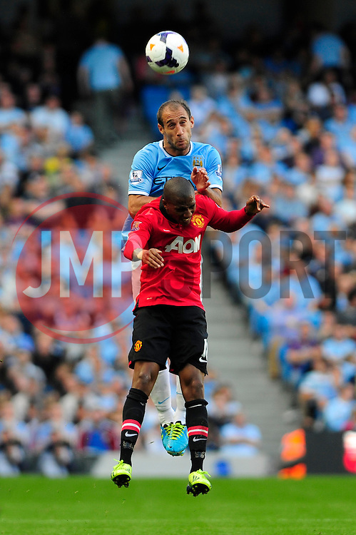 Manchester City's Pablo Zabaleta wins a header against Manchester United's Ashley Young - Photo mandatory by-line: Dougie Allward/JMP - Tel: Mobile: 07966 386802 22/09/2013 - SPORT - FOOTBALL - City of Manchester Stadium - Manchester - Manchester City V Manchester United - Barclays Premier League